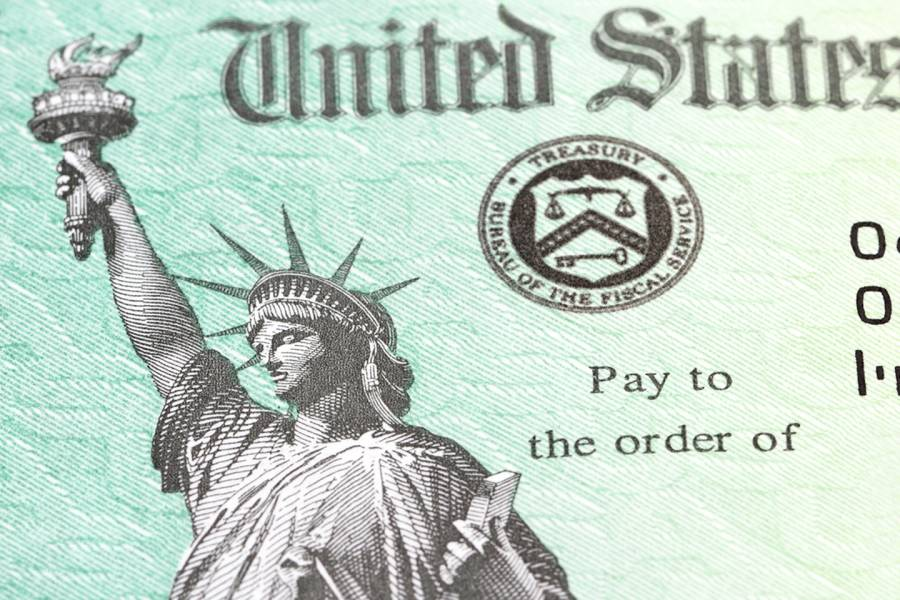 """The image is a close-up on a check that has the statue of liberty is on a light green background. Text that reads """"United States"""" is at the top of the image, the Bureau of Fiscal Services seal is in the middle, and text that reads """"pay to the order of"""" is below the seal."""