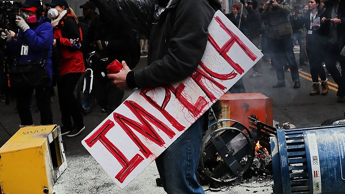 """Protester standing with sign that reads """"Impeachment"""" in Red"""