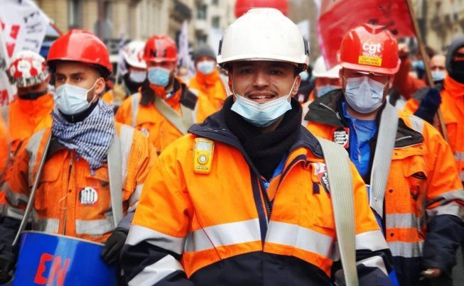 Three workers in orange safety wear wearing hard hats in front of a crowd of similarly dressed workers.