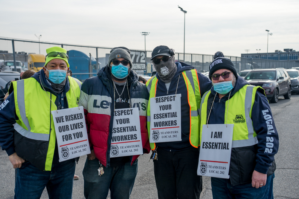 Four workers from Hunts Point in the Bronx stand wearing high-visibility jackets and protest signs around their neck while on strike.