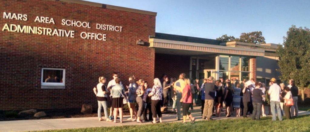 Group of people congregate outside the Mars Area School Administrative Office.