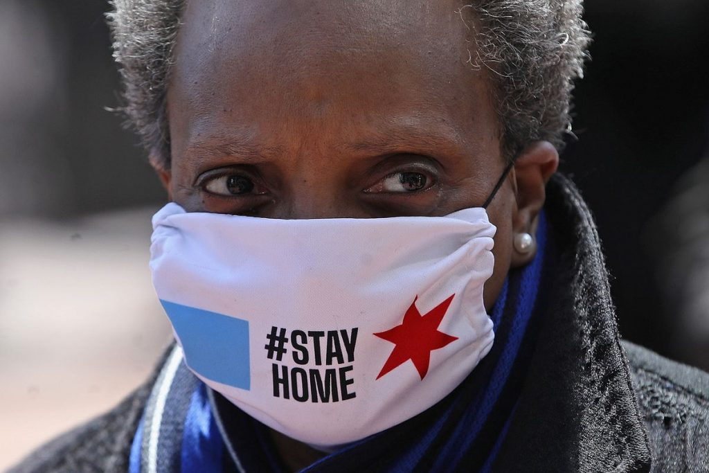 The photograph shows Chicago mayor Lori Lightfoot wearing a mask with the hashtag Stay at Home.