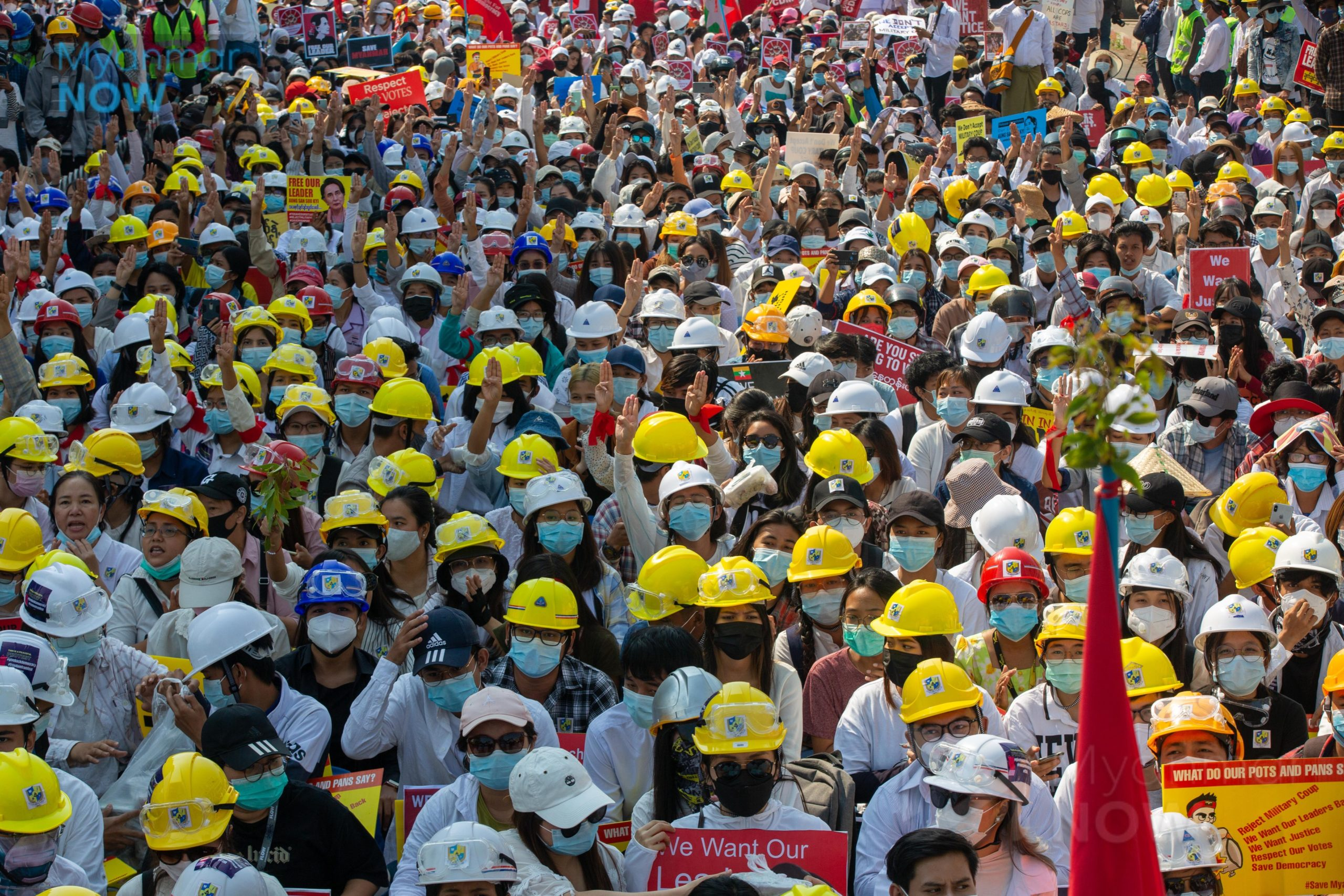 The entire frame of the photo is packed with Myanmarese workers, many of whom are wearing yellow or white hard hats. Most of them are wearing masks, and many are holding one hand in the air, palm forward, with the thumb tucked across the palm.