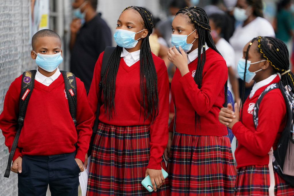 The photo shows a group of Catholic school students in New York City, masked, on their way to school.