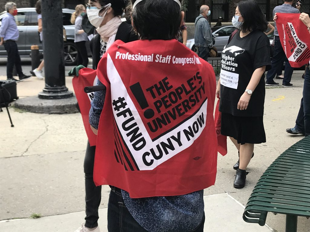 """Someone with short dark hair stands with their back to the viewer. On their back, they are wearing a piece of red cloth that says """"Professional Staff Congress. The People's University. #FundCUNYNow!"""" In the background, there are other people marching and carrying similar signs."""