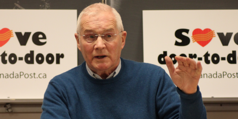 An image of Ernie Tate wearing a blue sweater and white collared shirt with his hand up in speaking.