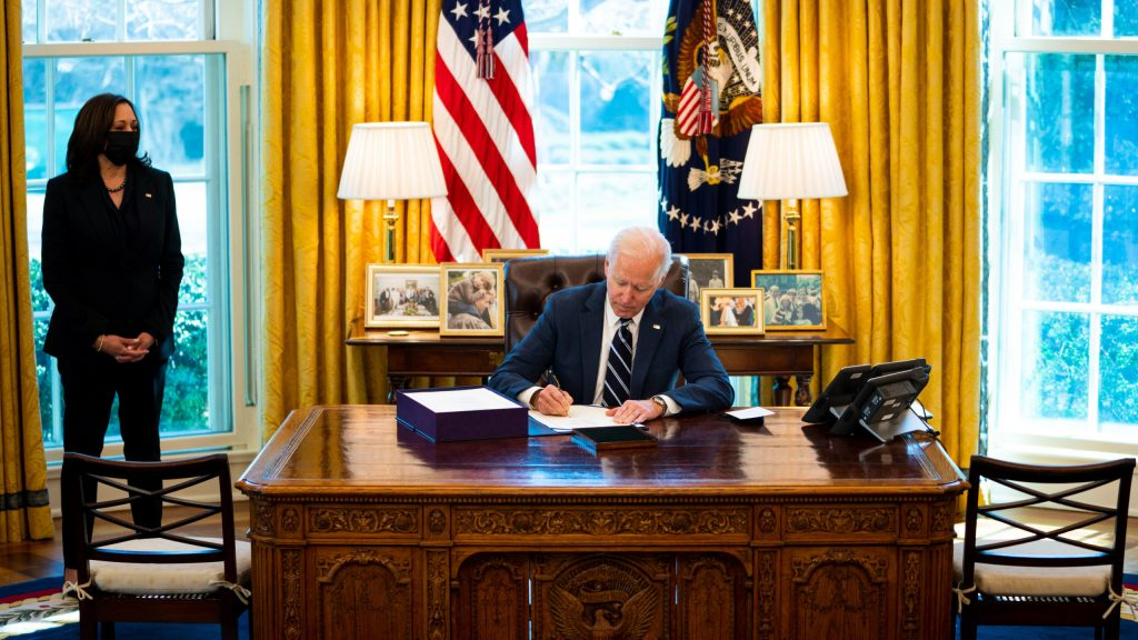 The photo shows President Joe Biden signing the stimulus bill on Thursday, March 11, in the Oval Office, as Vice President Kamala Harris looks on.