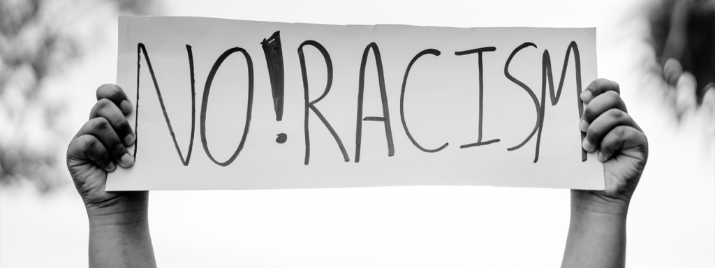 The photo shows a sign that reads No Racism! being held in the air.
