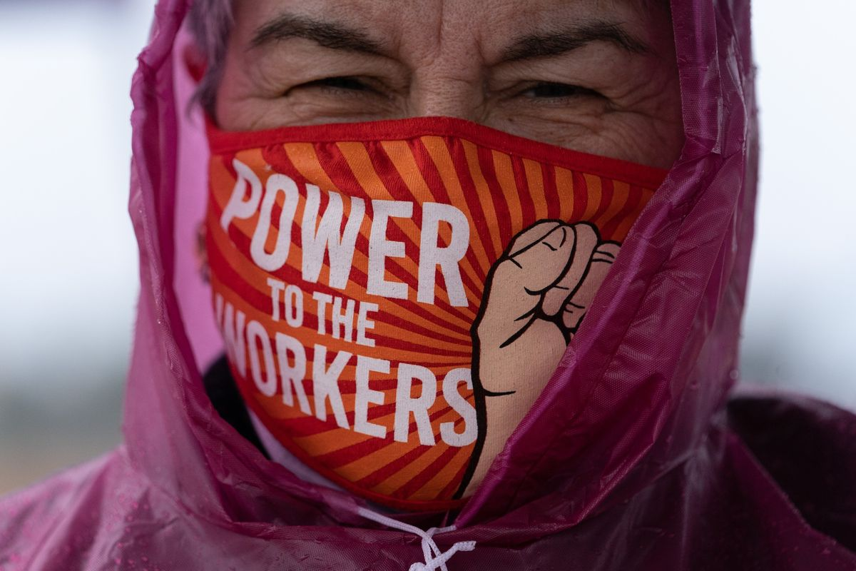 A person wears a face mask with the words Power to the Workers on it along with a clenched fist.