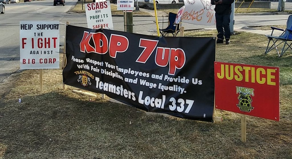 The photo shows signs supporting the Teamsters struggle, on a main road near the bottling plant.