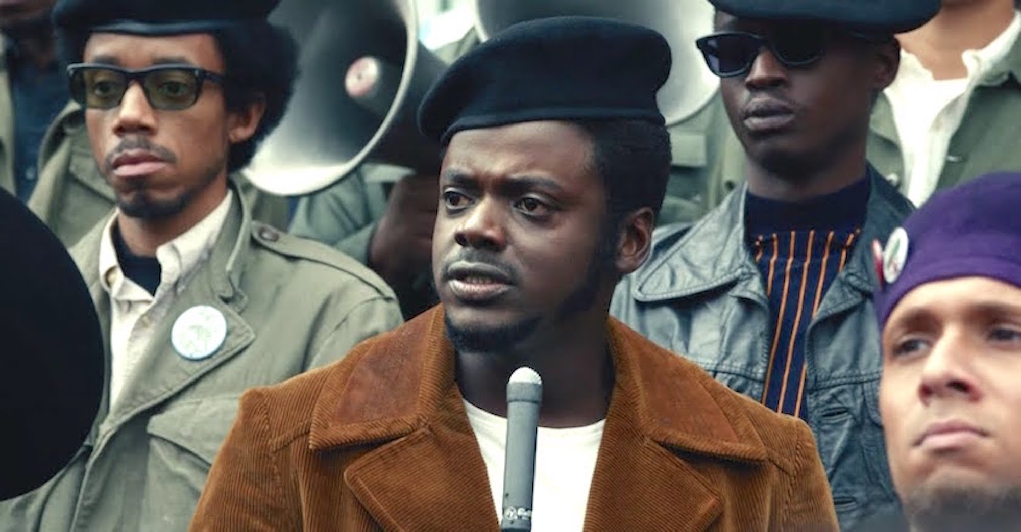 The actor Daniel Kaluuya in character as Fred Hampton. He is standing in front of a microphone looking serious and concerned, with other Black activists standing behind him.
