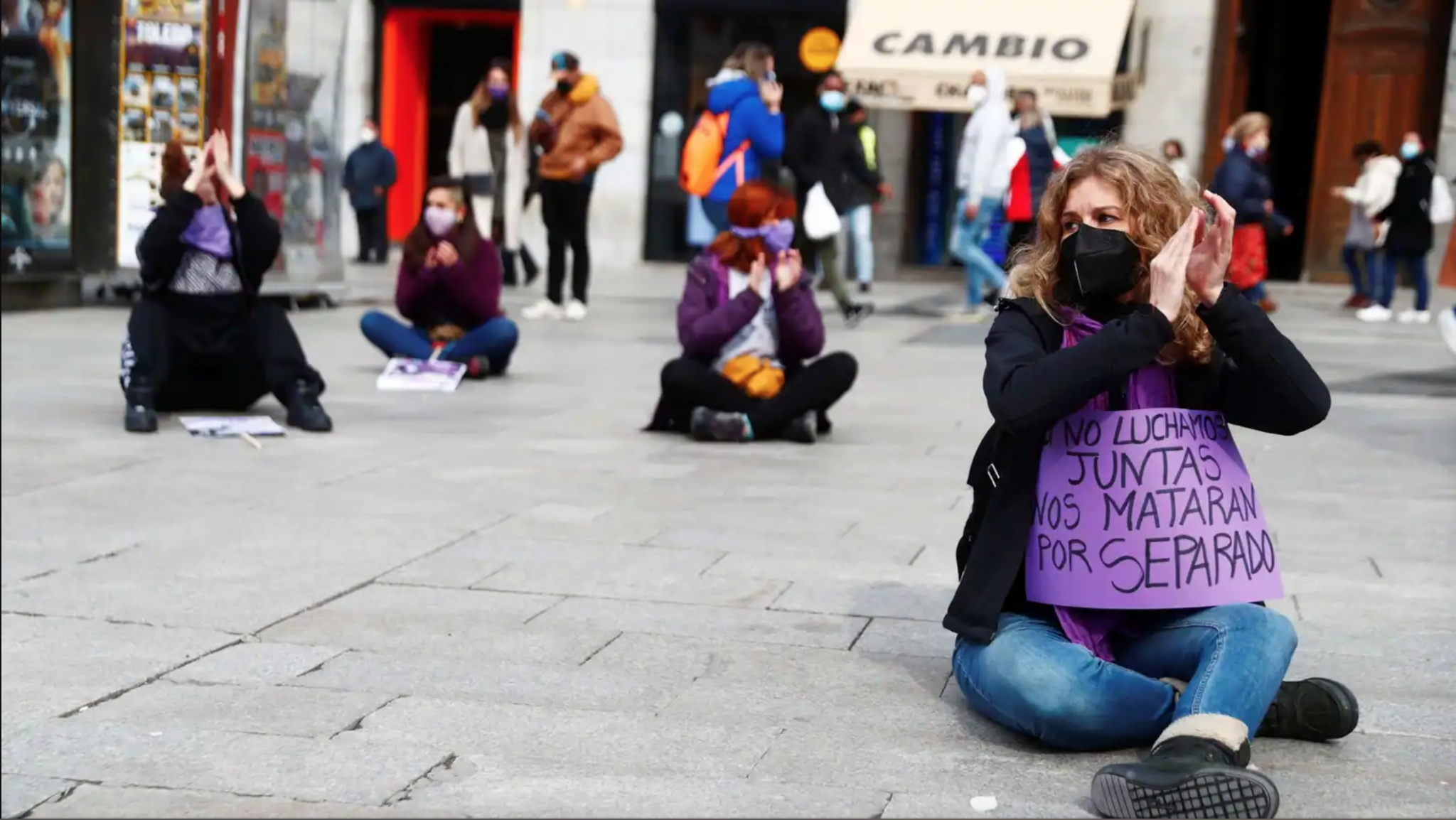 feminist protesters in Madrid sit on the ground holding signs on International Women's Day 2021.