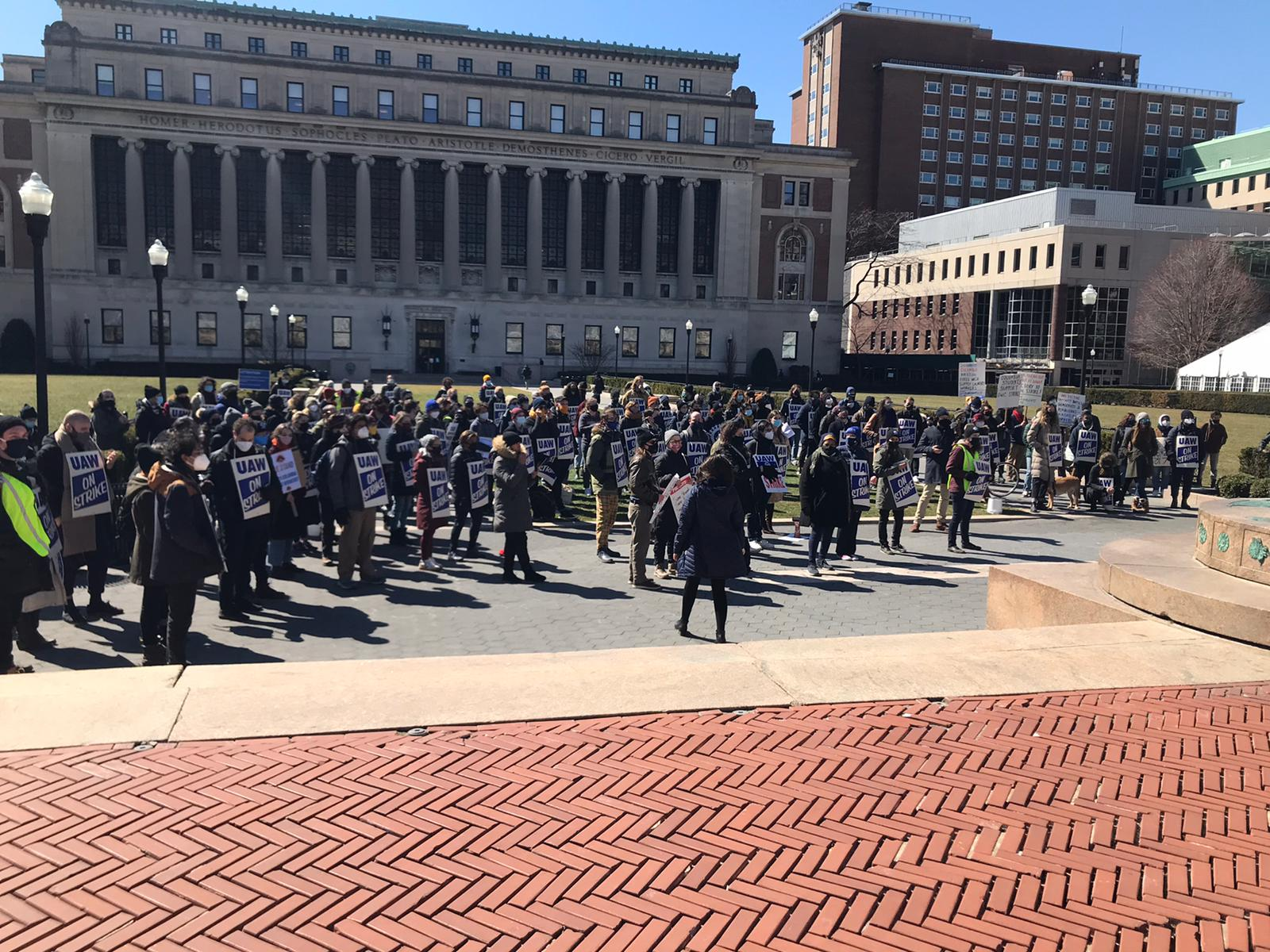 Grad students at Columbia on strike stand in front of the university listening to a speaker.