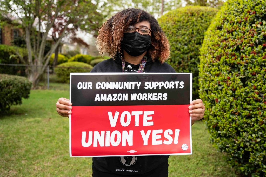 """Frances Wallace, a Black woman wearing glasses and a plan black mask, holds a sign that says """"Our Community Supports Amazon Workers: Vote Union Yes!"""""""
