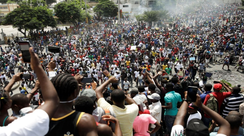 The photo shows a mass protest in the streets of Haiti.