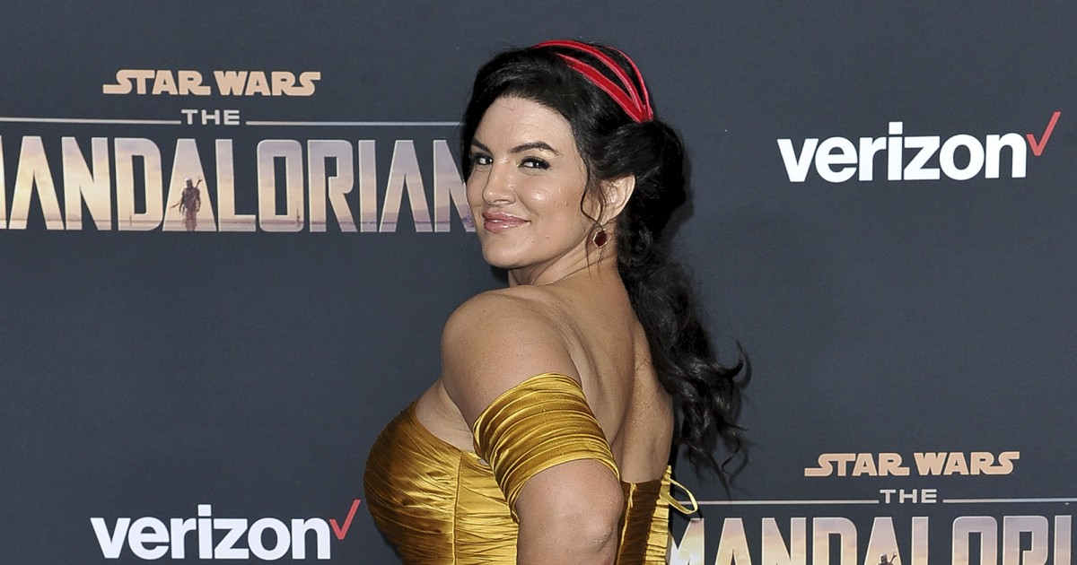Actor Gina Carano looks back in a yellow dress at an event for The Mandalorian.