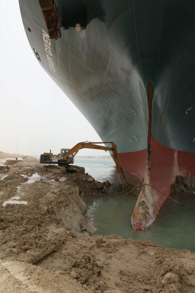 The photo shows a small bulldozer moving earth as it tries to free a huge container ship grounded in the Suez Canal.