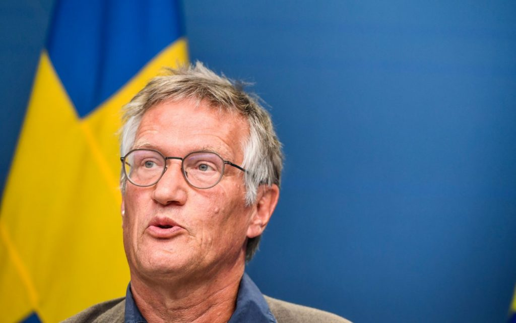 Swedish state epidemiologist Anders Tegnell speaks in front of a Swedish flag.