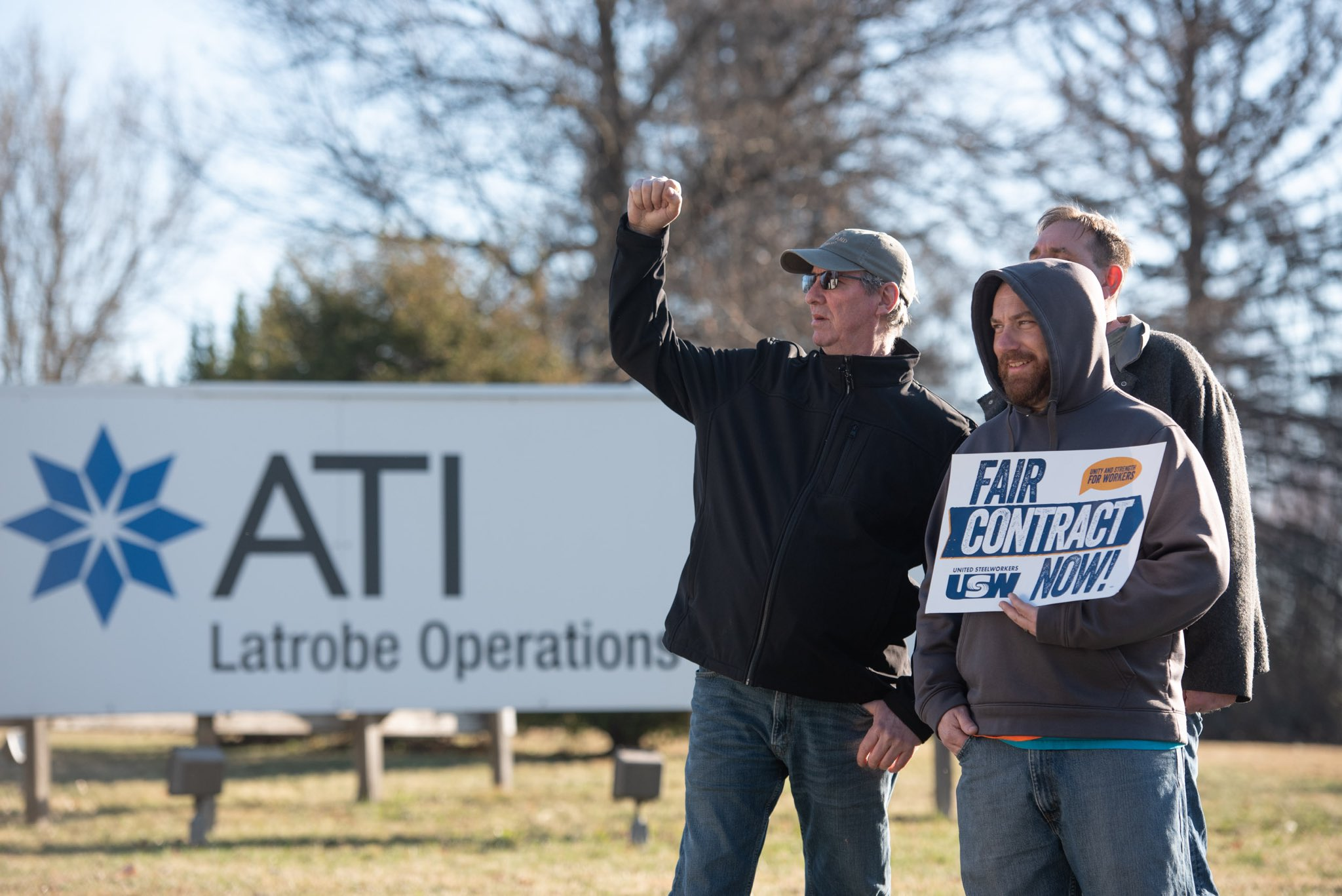 """Two steel workers on strike stand with their fists in the air and a sign that says """"Fair Contract Now,"""" the background is a sign for ATI."""