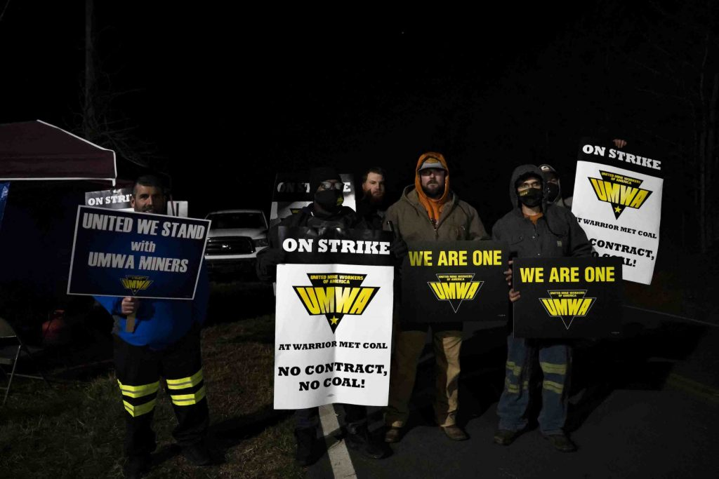 """In the dark, striking miners hold up signs saying """"No contract, no coal."""""""