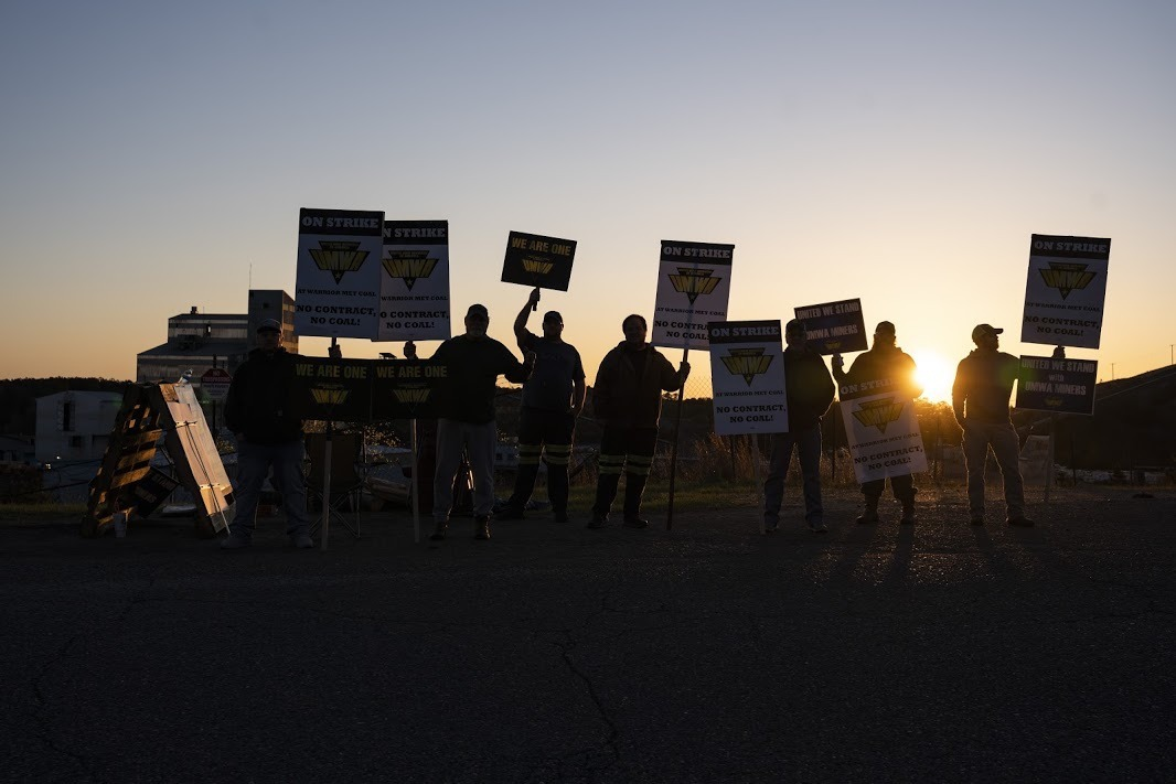 With the sun setting in the background, striking coal miners with Warrior Met stand holding up signs. They look silhouetted.