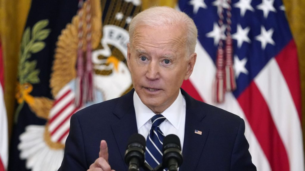 U.S. president Joe Biden stands at a podium in front of a U.S. flag making a speech while pointing his finger.