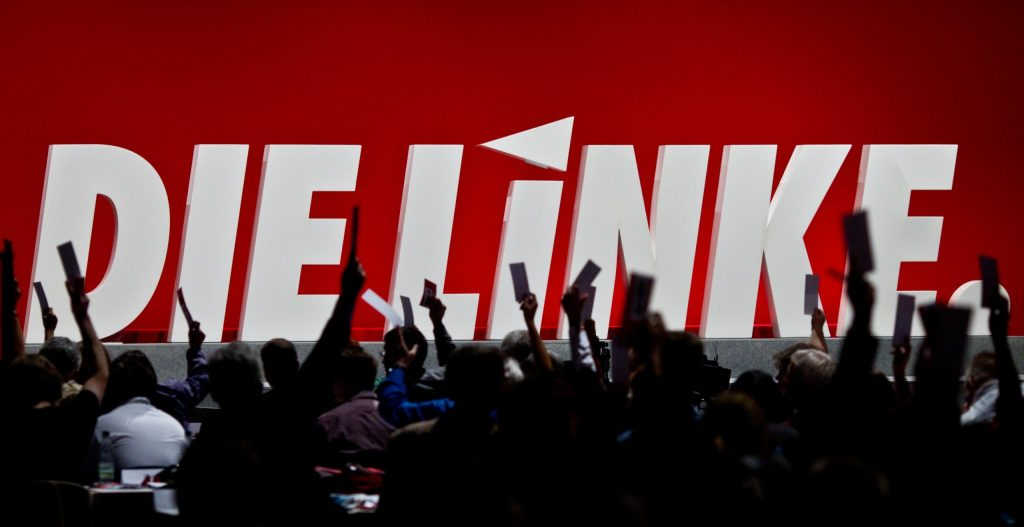 """Silhouette of a crowd cheering in front of a huge sign that says """"DIE LINKE,"""" the German leftist party."""