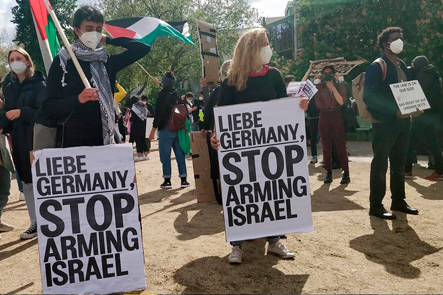 """German protesters hold signs that read """"Liebe Germany. Stop arming Israel."""" In the background, people are waving Palestinian flags."""