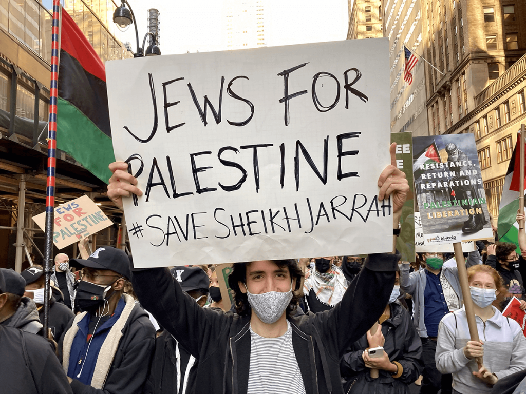 """A young adult wearing a medical mask holds a sign above their head that reads """"JEWS FOR PALESTINE, SAVE SHEIKH JARRAH"""""""