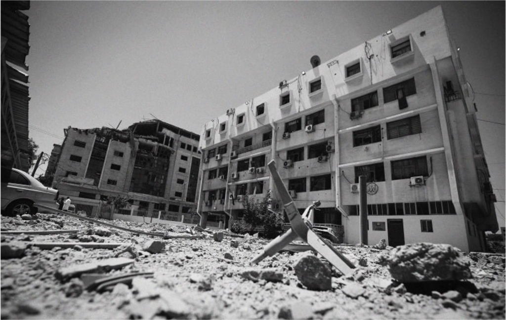 A black and white picture of the Gaza Ministry of Health. The building is damaged, with detritus in front.
