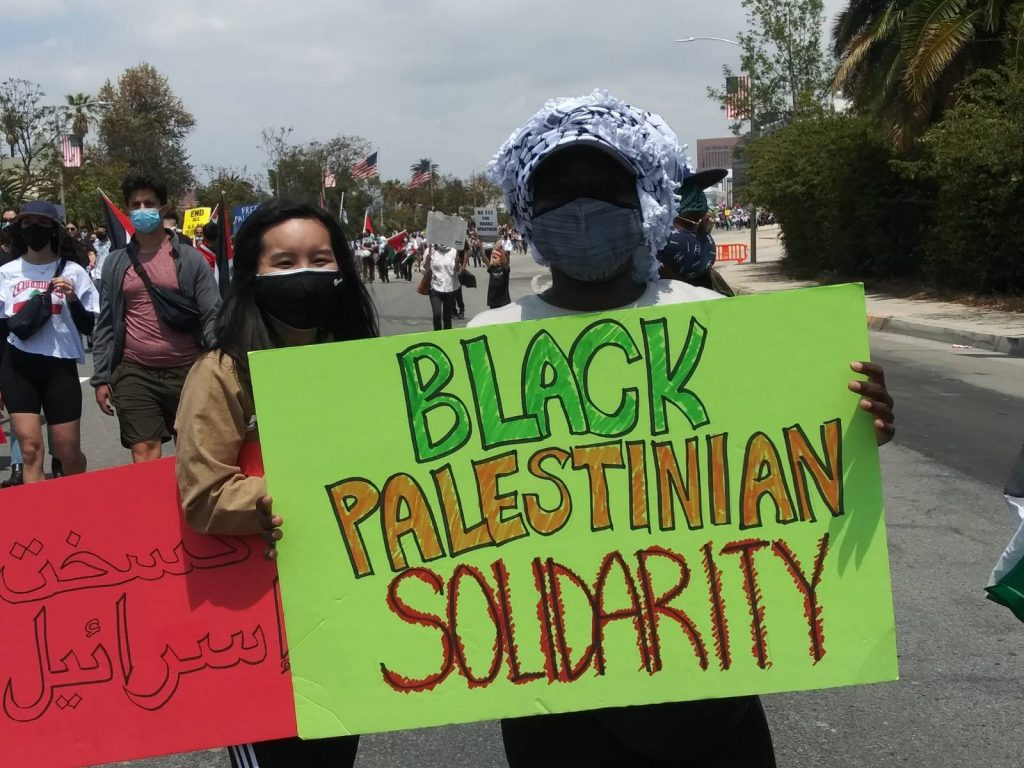 """A black woman with a face mask stands with a green sign that says """"Black Palestinian Solidarity"""""""
