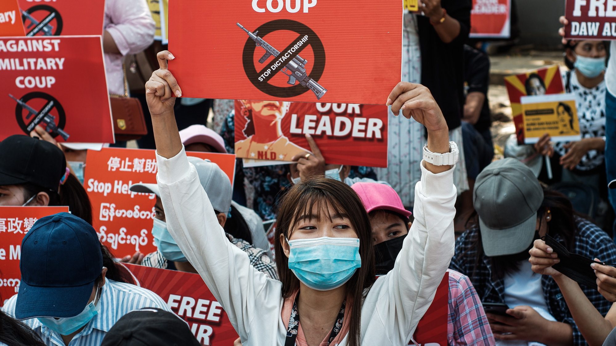 """Person wearing a blue face mask holds a red sign that says """"stop dictatorship"""" in front of a crowd of protesters."""