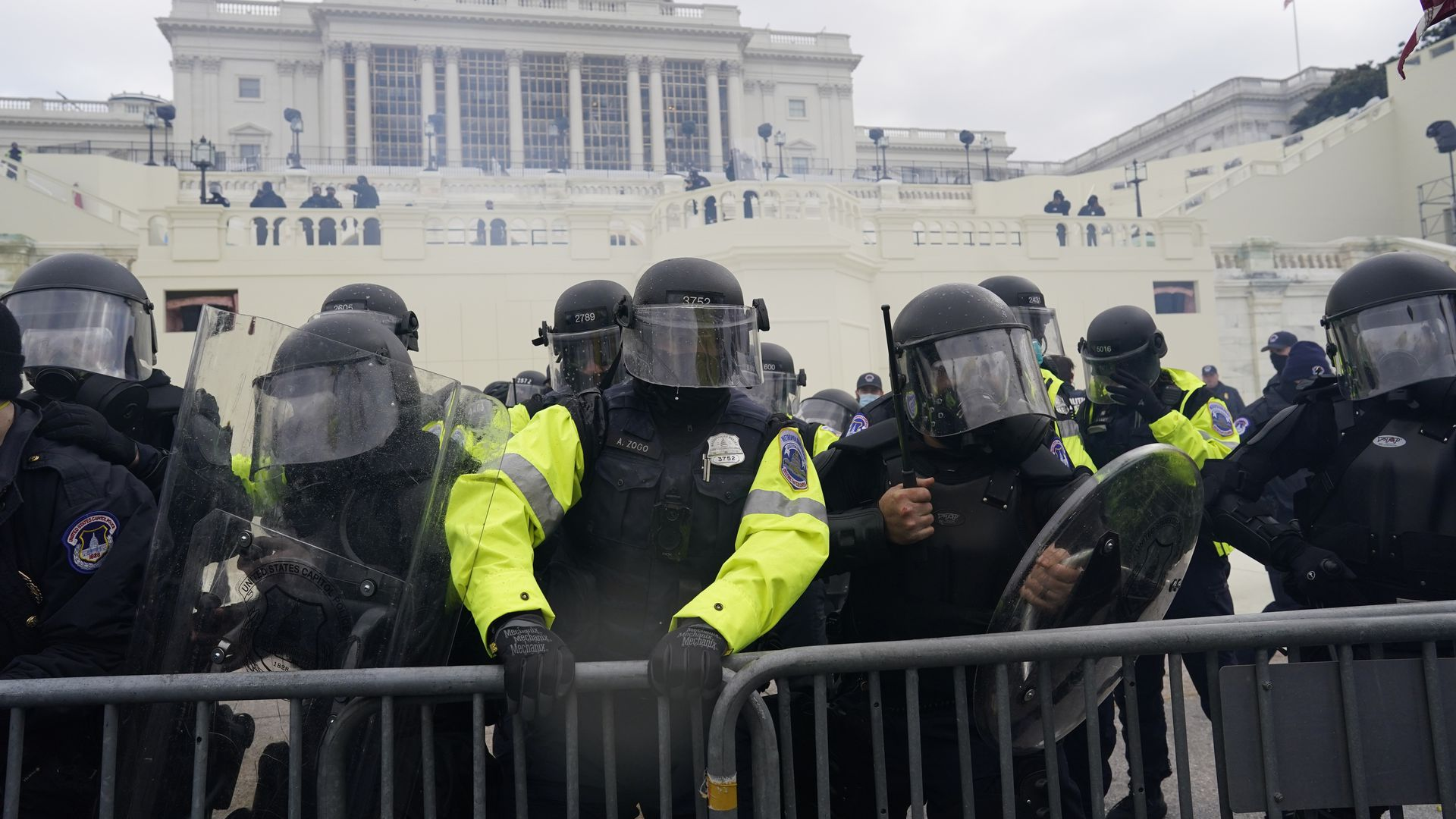 Police officers in riot gear stand against barriers during the Jan 6 riot. The Capitol building is in the background.