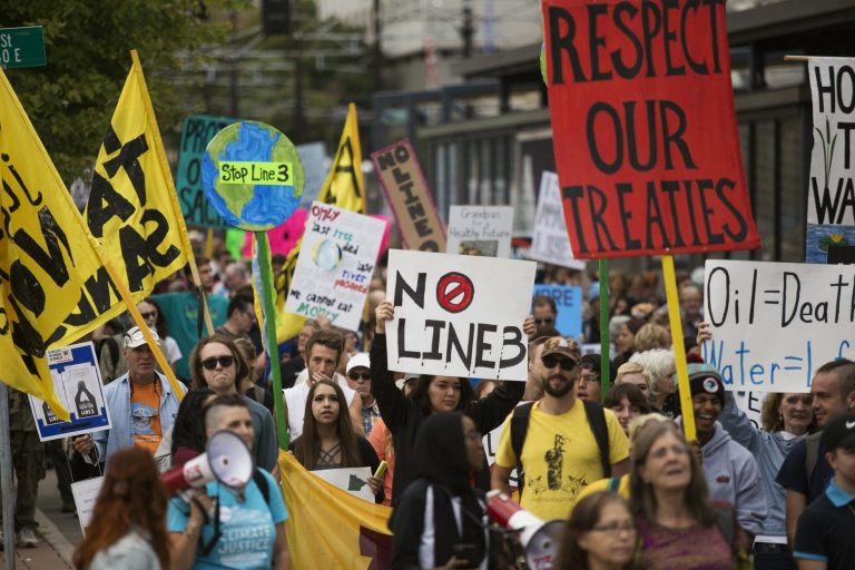 Protesters in Minnesota march and hold signs in protest of the Line 3 pipeline.
