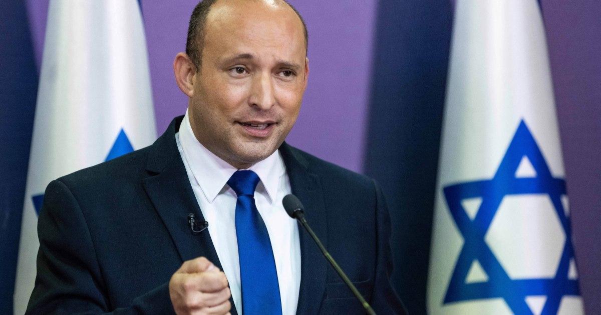 New Israeli Prime Minister Naftali Bennett stands in front of two Israeli flags.