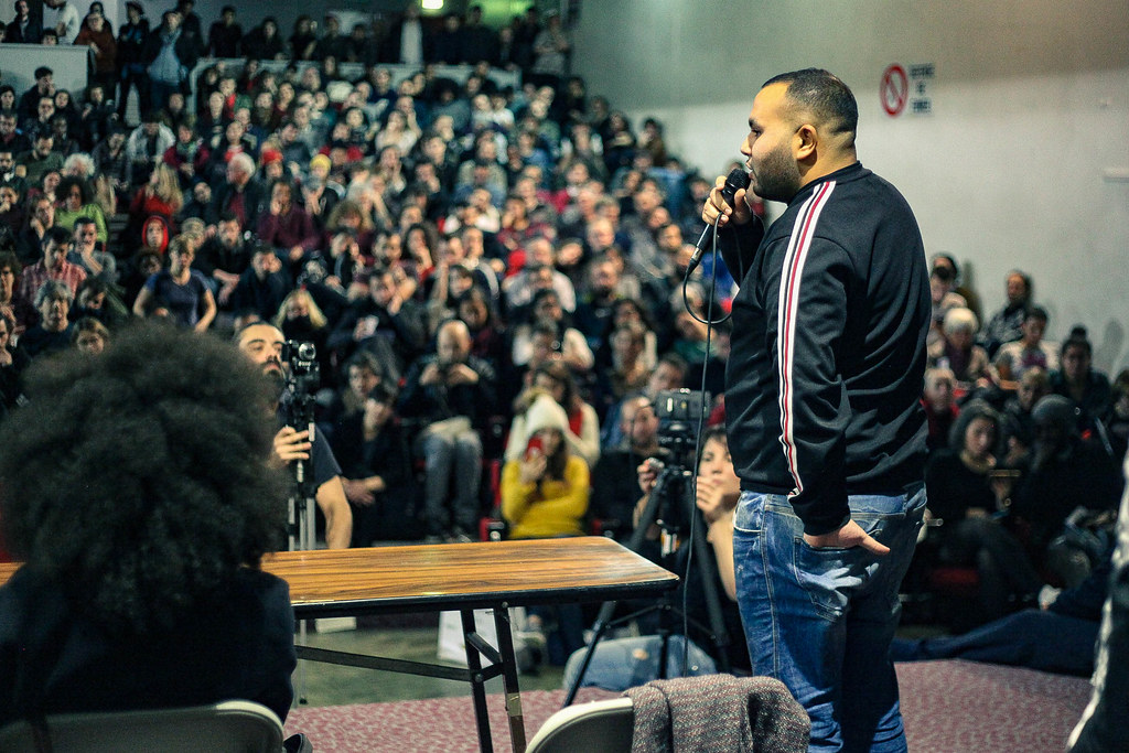 Anasse Kazib, wearing jeans and a sweatshirt, uses a microphone to address a crowd