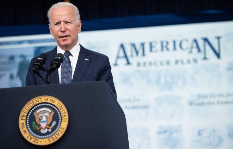 Joe Biden stands behind a podium giving a speech