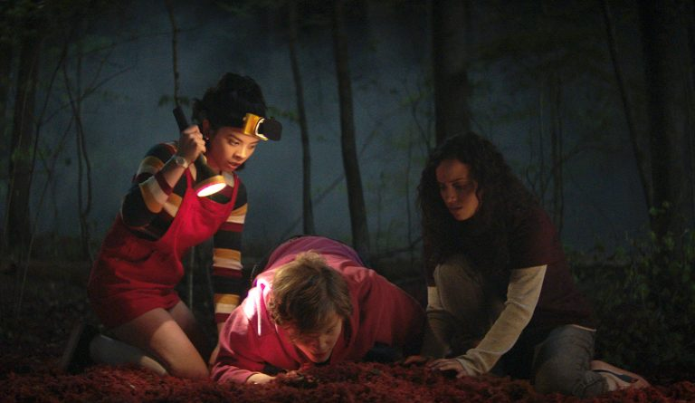 Three teenagers are kneeling down in a dark forest, one is holding a flashlight and the other is inspecting the ground. It's a scene from Netflix's Fear Street series.