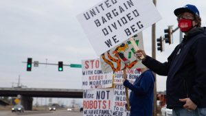"""Frito Lay workers stand in front of traffic lights, the one in the front is holding a sign that says """"united we bargain, divided we beg."""""""