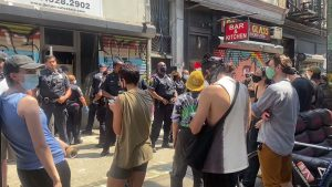 """Protesters stand facing NYPD officers outside """"The Gym,"""" an organizing space in Bushwick, Brooklyn."""