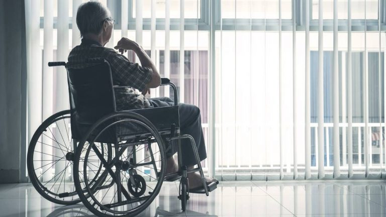 Elderly person sitting in a wheelchair with their back facing the camera in front of a window with the shutters open.