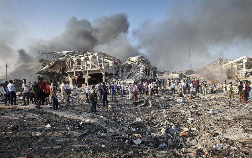 Image of rubble and a lot of smoke in the background. People stand in front of the wreckage.