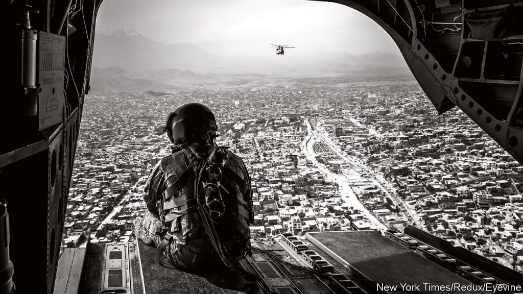 A black and white image of a U.S. soldier looking down at Afghanistan from a helicopter