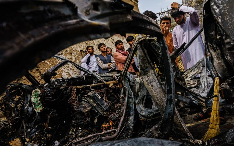 Several family members and neighbors of the Ahmadi family gather around a car destroyed by the drone strike.