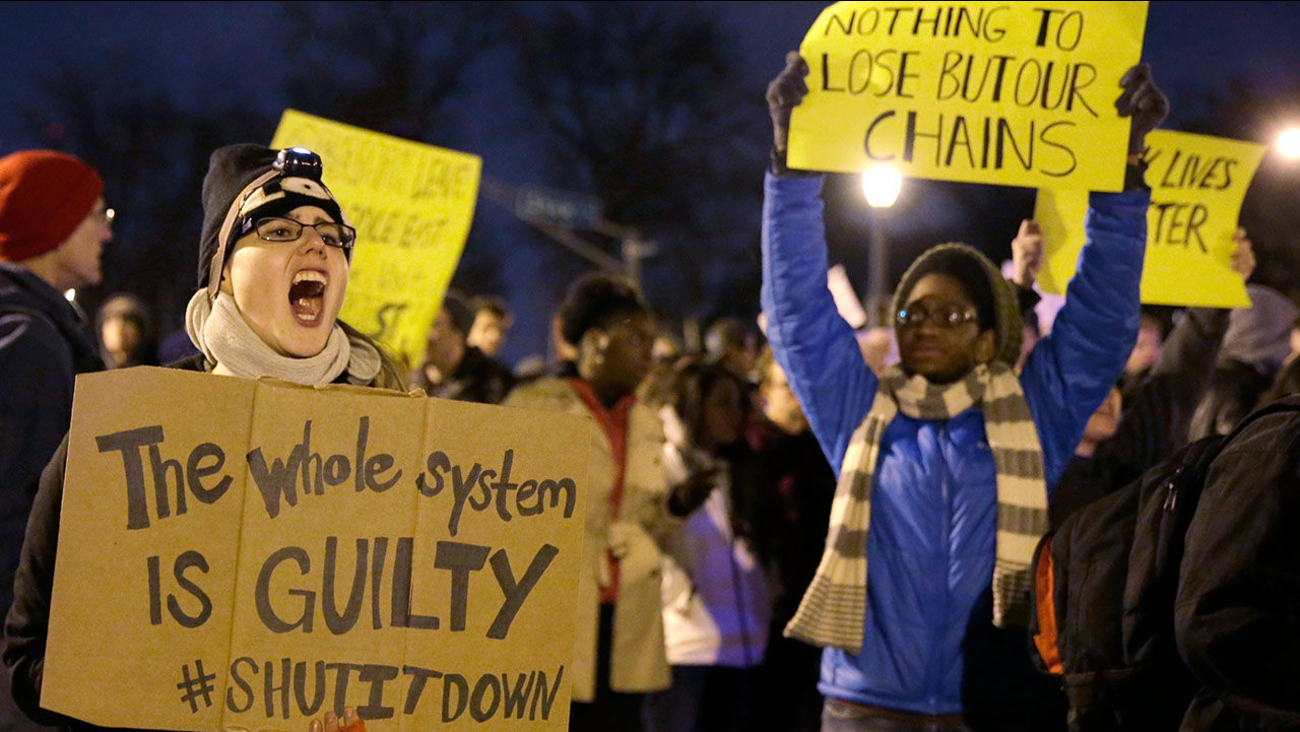 """Protester holds a sign that says """"The whole system is GUILTY #SHUTITDOWN. Another protester behind them wearing a blue sweater and yellow striped scarf holds a sign that reads """"Nothing to lose but our chains."""""""