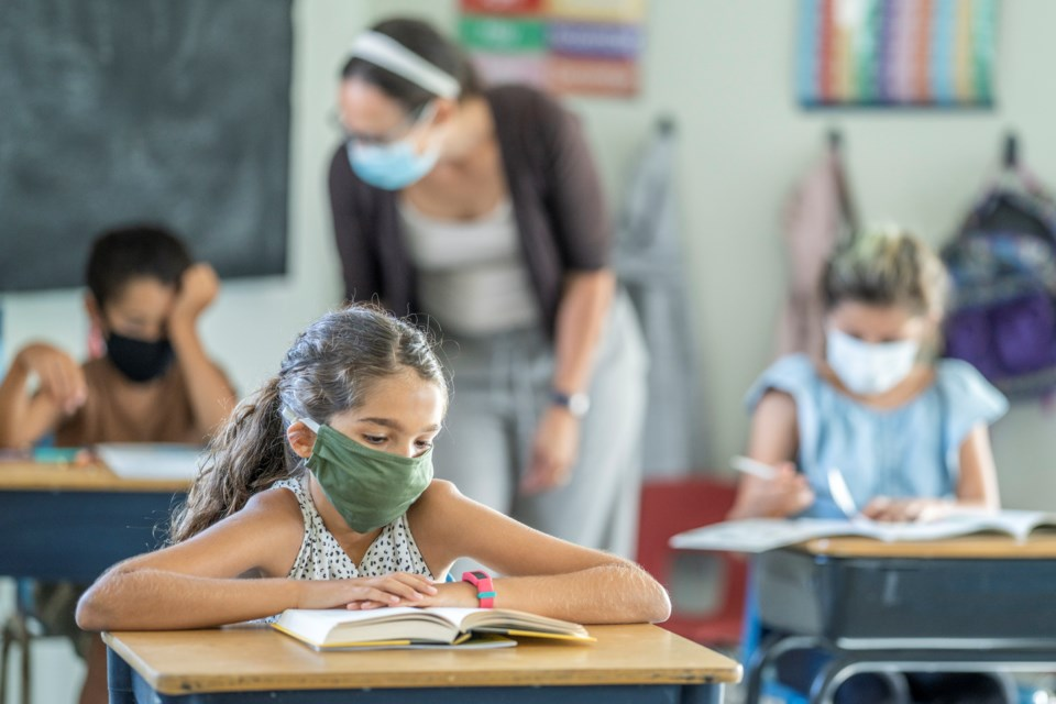 Child with long hair wearing a green mask is sitting at a desk in the front reading a book. Their teacher is wearing a white headband, white tanktop,brown cardigan, and blue jeans behind them.