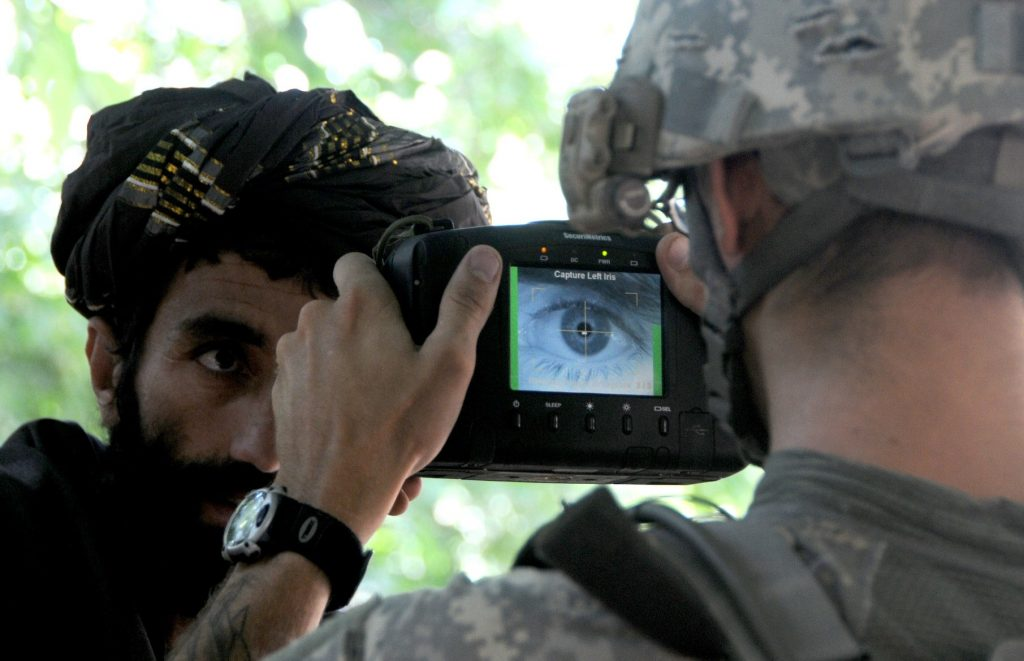 A U.S. soldier in army uniform and helmet is shown from behind while taking a close-up photo of the eye of an Afghan man with a bear and turban.
