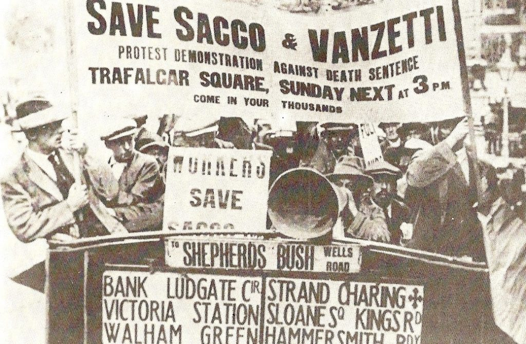 """A photo from the 1920s of British workers holding a banner that says """"Save Sacco & Vanzetti"""": Protest Demonstration Against Death Sentence, Trafalgar Square, Sunday Next at 3pm, Come In Your Thousands"""