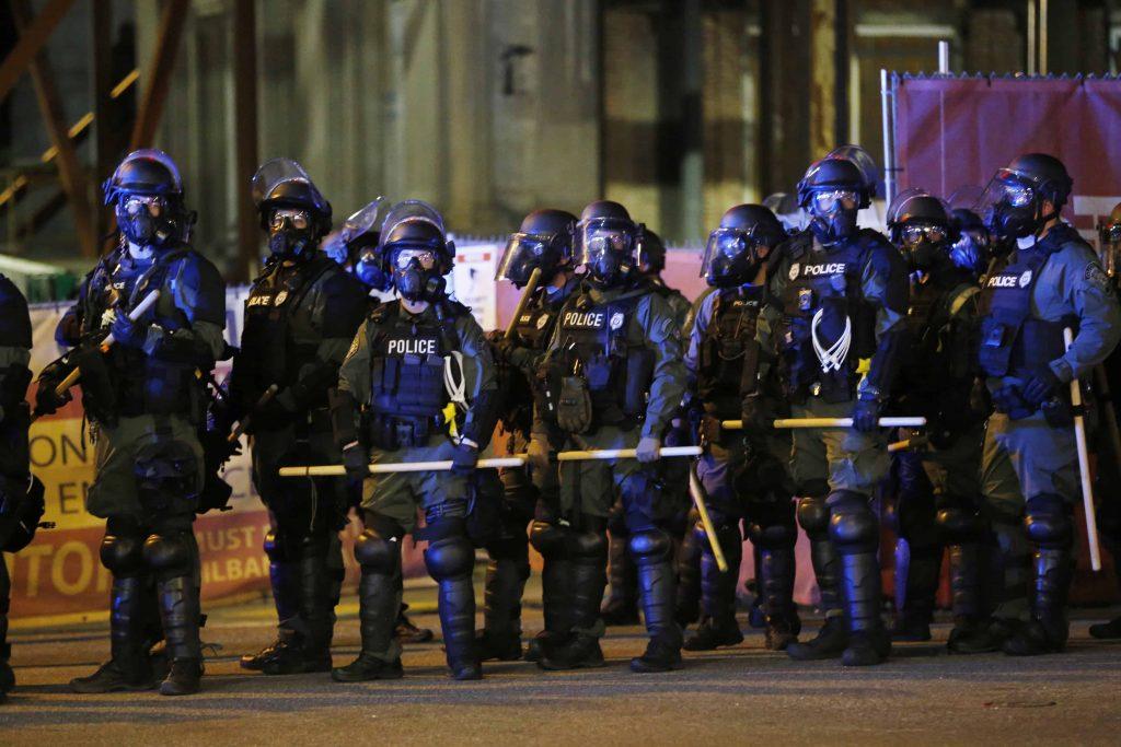 A line of cops wearing riot gear