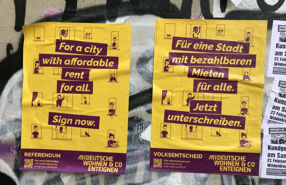 """Two yellow posters side by side, the left one says """"For a city with affordable rent for all, sign now."""" The right sign says the same in German."""